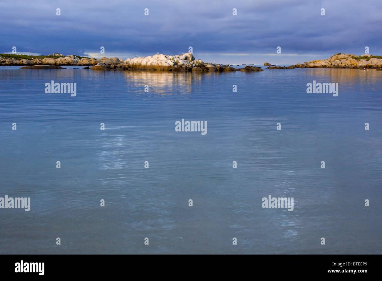L'eau bleue et un ciel bleu avec des îles de roches dans l'arrière-plan Photo Stock