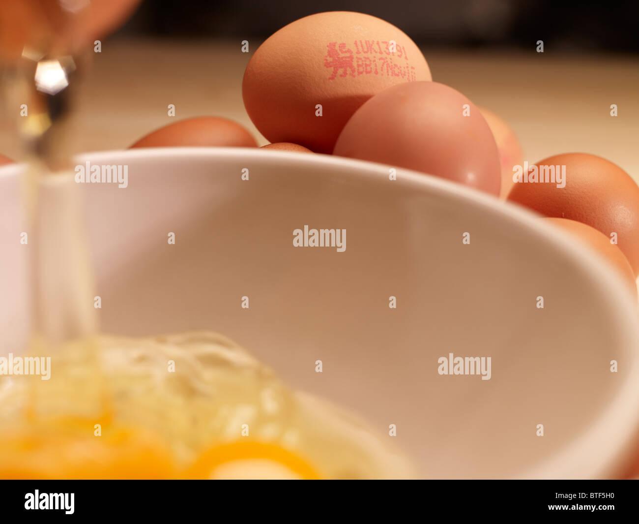La fissuration oeuf dans un bol Photo Stock