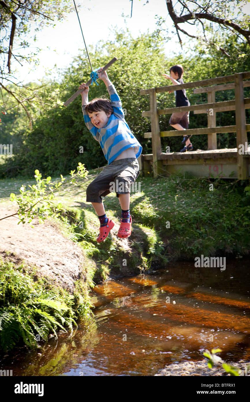 Boy swinging sur une corde Photo Stock