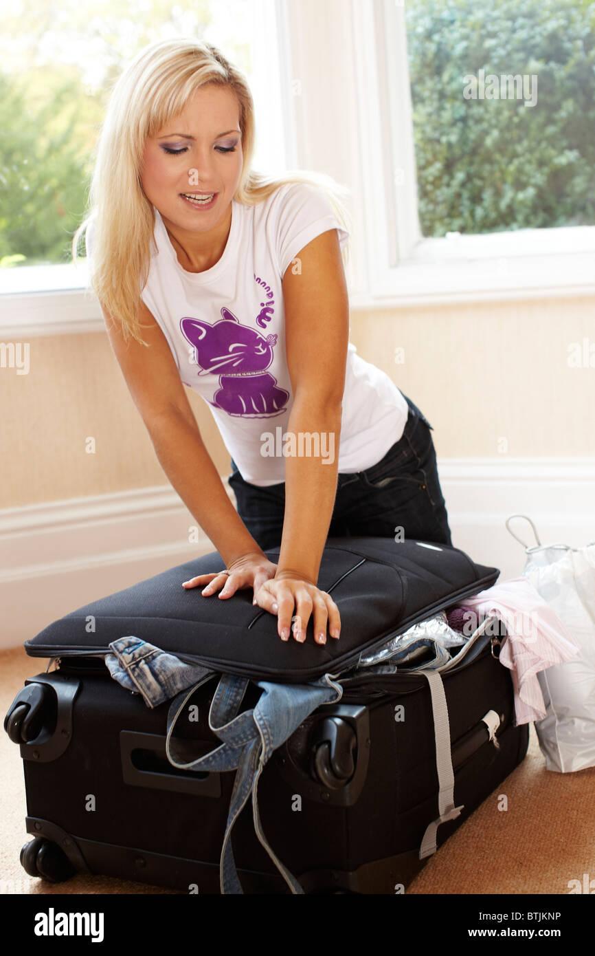 Fille de la difficulté à fermer suitcase Photo Stock
