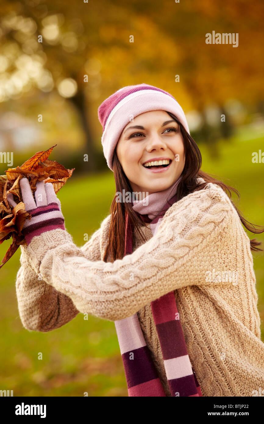Fille brune la collecte les feuilles d'automne Photo Stock