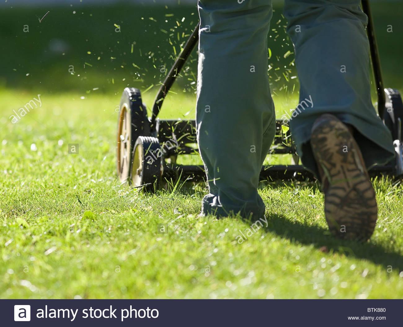 Couper l'herbe avec une tondeuse à gazon. Photo Stock
