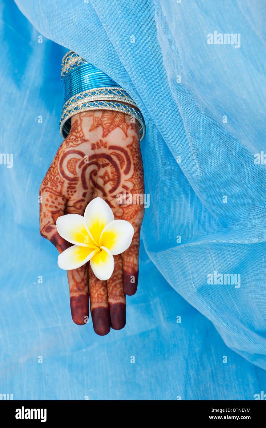 Indian girl wearing a blue sari de henné mains tenant une fleur de frangipanier. L'Inde Photo Stock