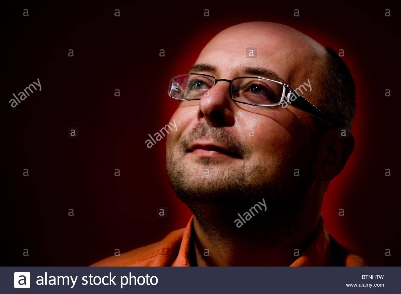Homme chauve avec des lunettes à une expression optimiste Photo Stock