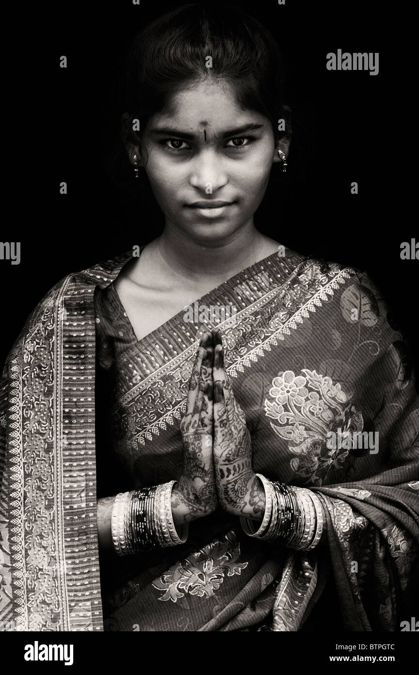 Indian girl wearing silk sari traditionnel au henné la prière les mains. L'Inde. Sepia Photo Stock