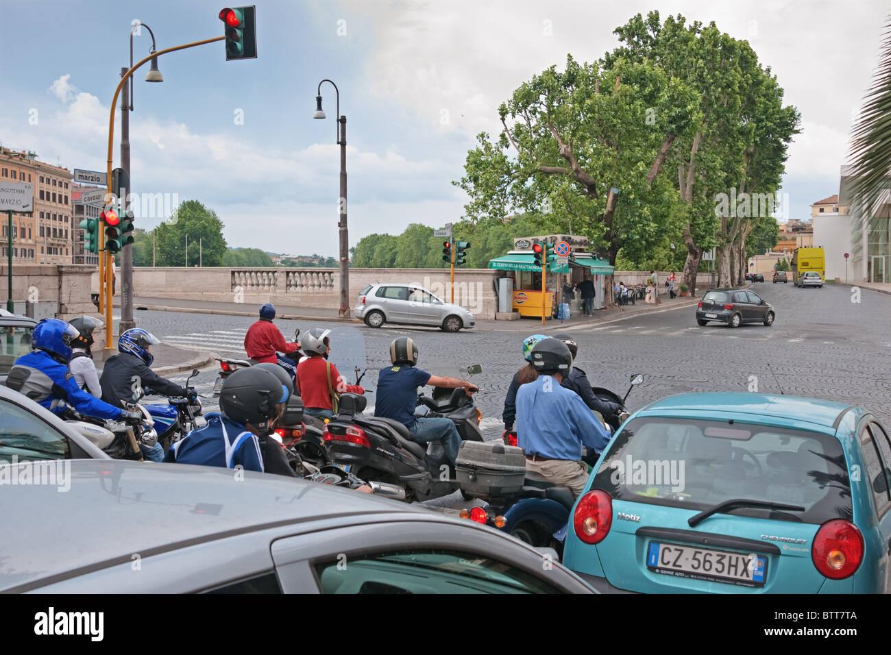 Scooters sur carrefour en attente de vert dans la fin de journée de travail Rome Italie Photo Stock