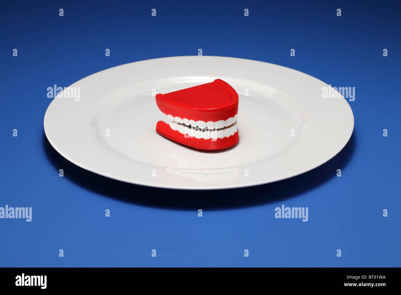 Un jeu de gencives et les dents en plastique sur une assiette blanche Photo Stock