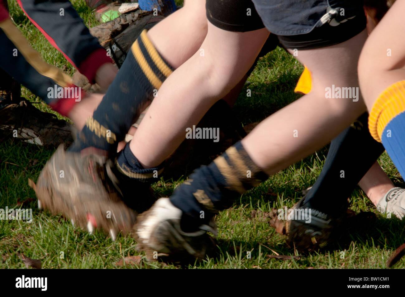 Les jeunes garçons à jouer au rugby dans une mêlée à l'extérieur en jeu à Photo Stock
