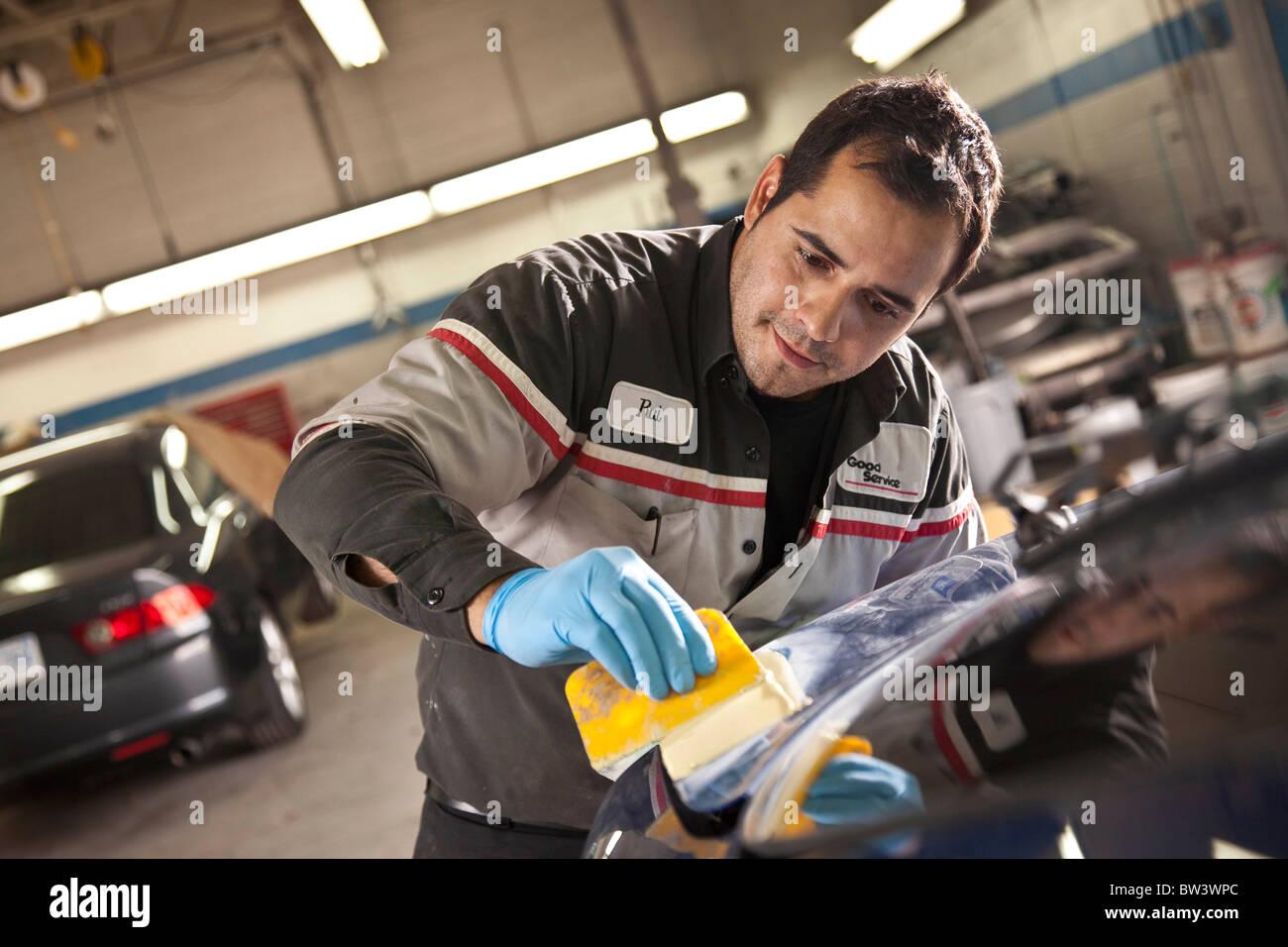 Mécanicien à l'aide de mastic pour boucher les trous Photo Stock