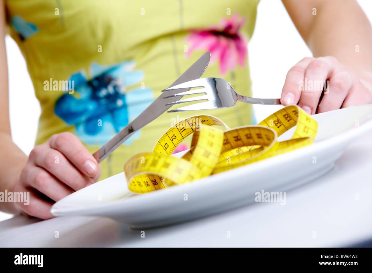 Close-up of female hands holding fourchette et couteau sur la plaque avec un ruban à mesurer en c Photo Stock