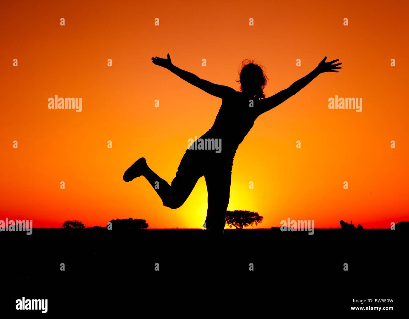 Silhouette d'une jeune femme sautant au coucher du soleil Banque D'Images