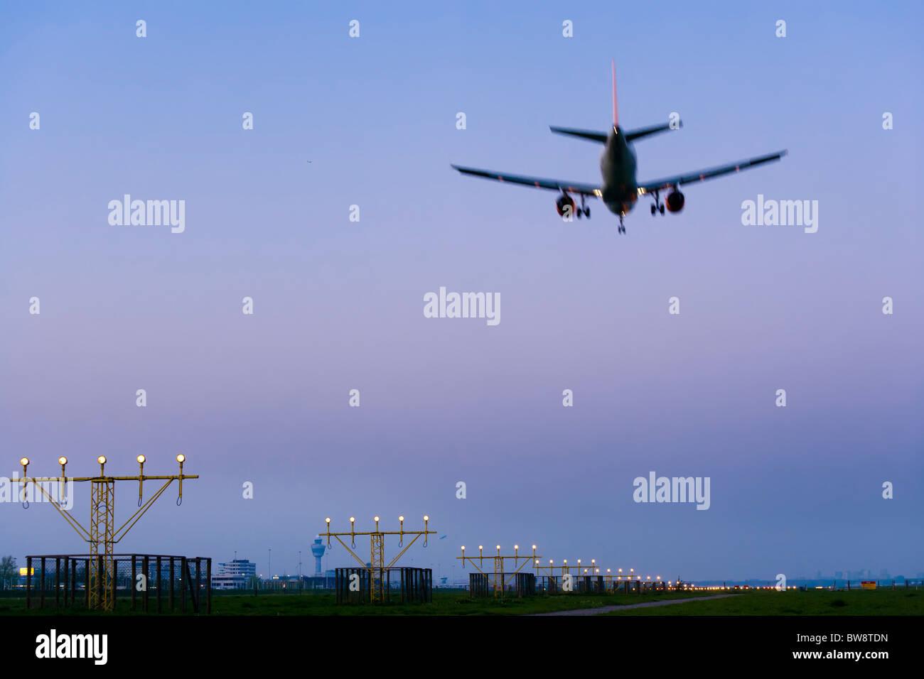 L'aéroport d'Amsterdam Schiphol au crépuscule. Avion avion qui approche, l'atterrissage, sur Photo Stock