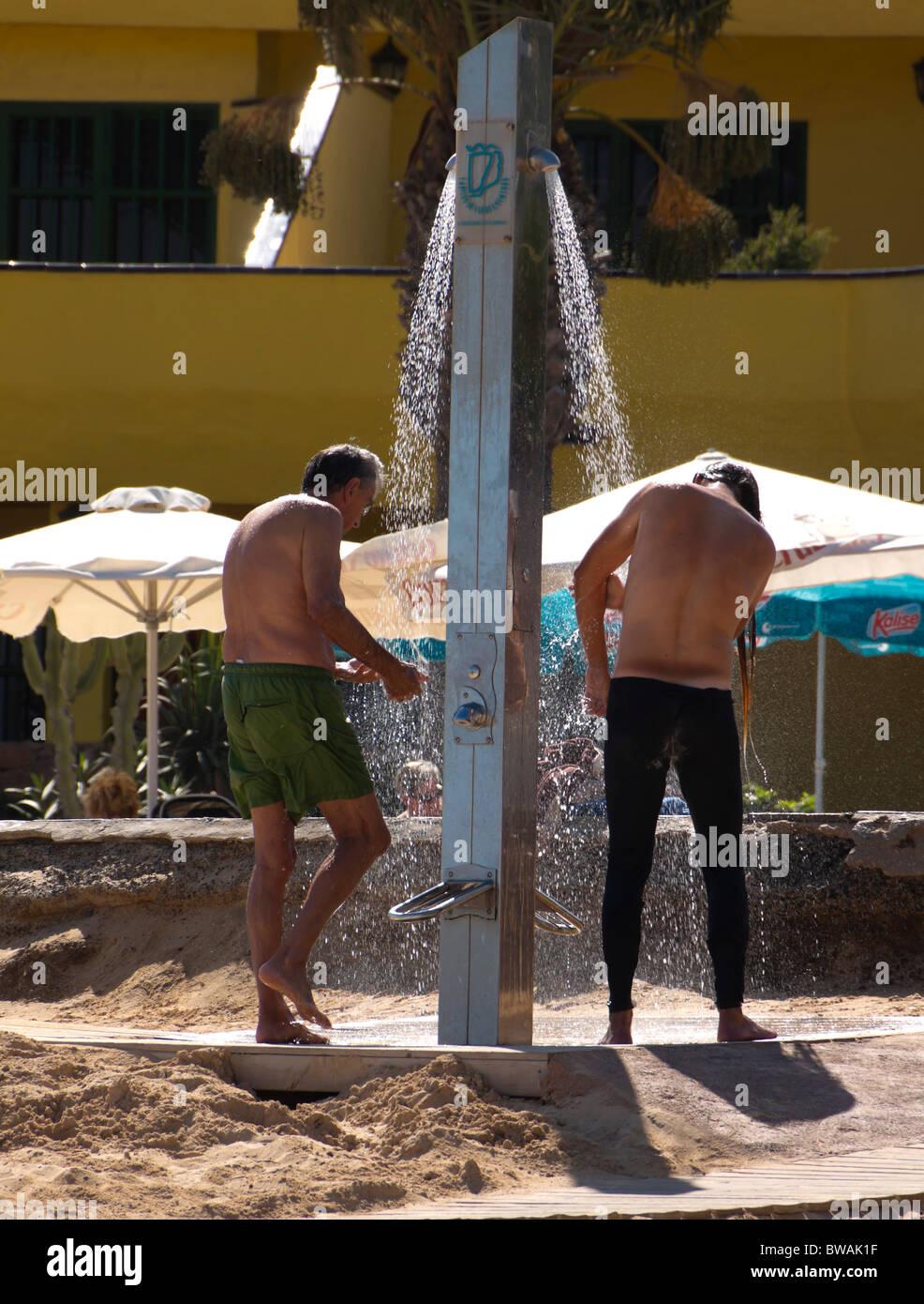Fuerteventura, Îles Canaries - Corralejo, les hommes la douche sur la plage. Photo Stock