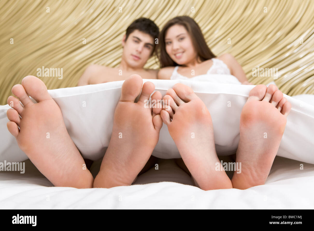Image de deux paires de pieds nus sur fond de happy couple lying under blanket Photo Stock