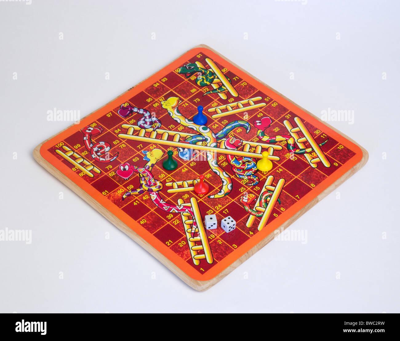 Jouets, jeux, jeu de société, jeu de serpents et échelles avec des dés et des compteurs pour les enfants sur un fond blanc. Banque D'Images