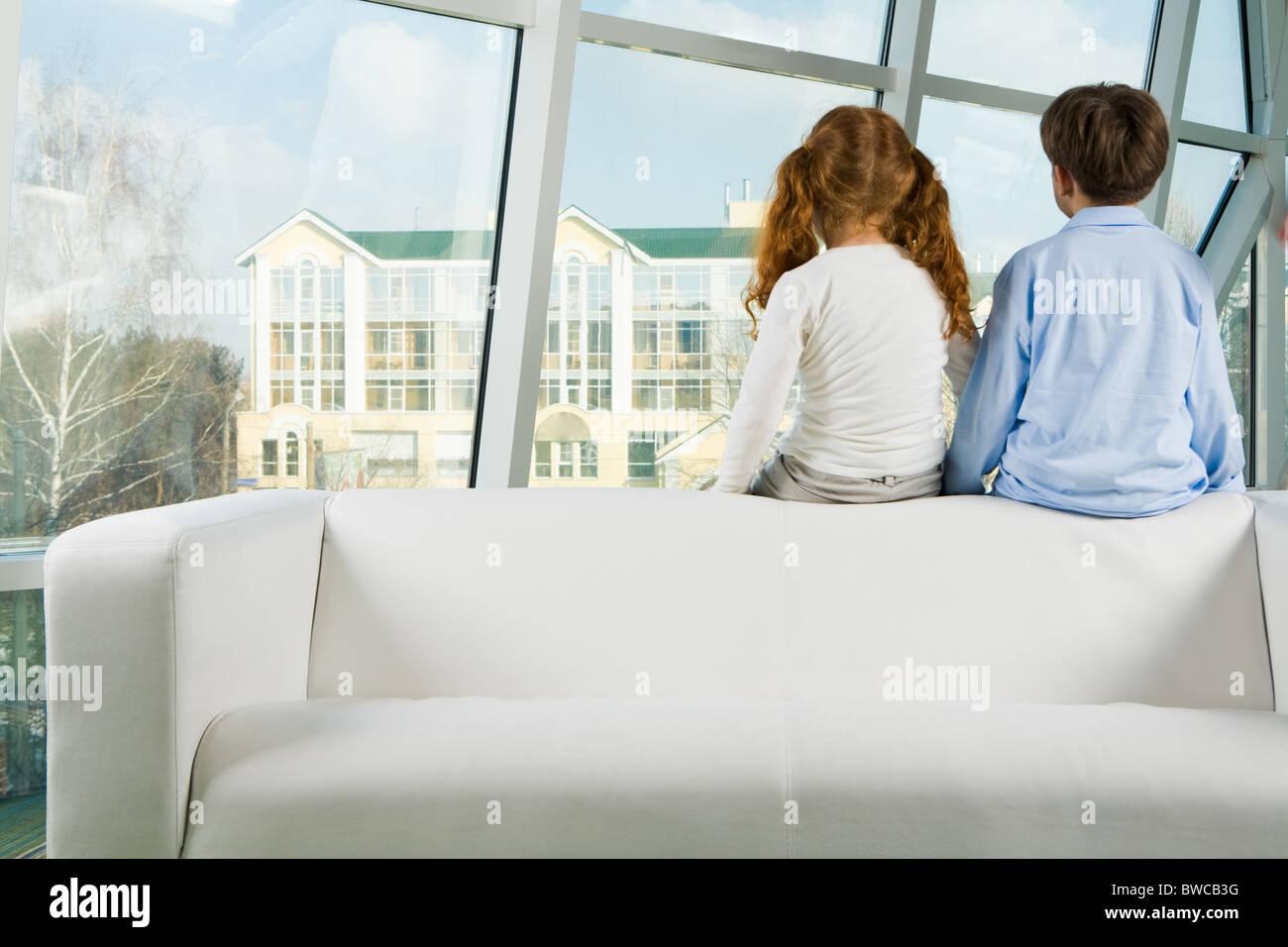 Vue arrière de deux enfants assis sur le canapé blanc et à la recherche d'une fenêtre Banque D'Images