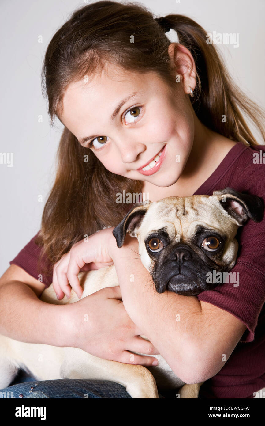 Studio portrait of smiling girl (10-11) holding pug Photo Stock