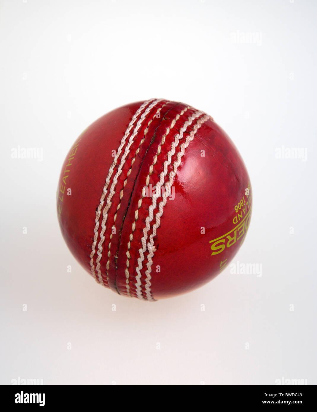 Sport, jeux de balle, le cricket, le cuir cousu main rouge balle de cricket sur un fond blanc. Photo Stock