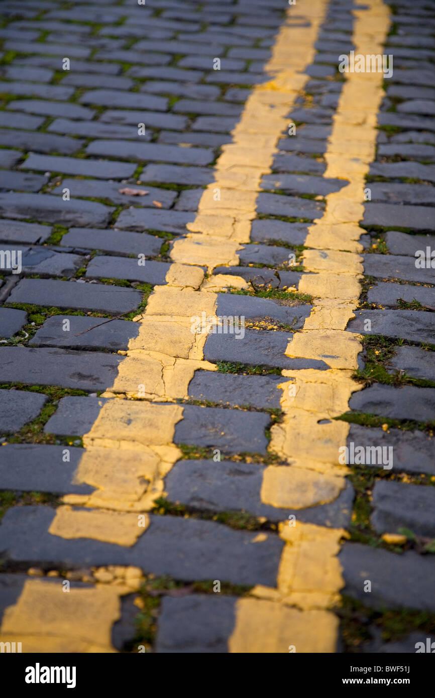 Les lignes jaunes indiquant double restriction parking interdit dans une rue pavée road Photo Stock