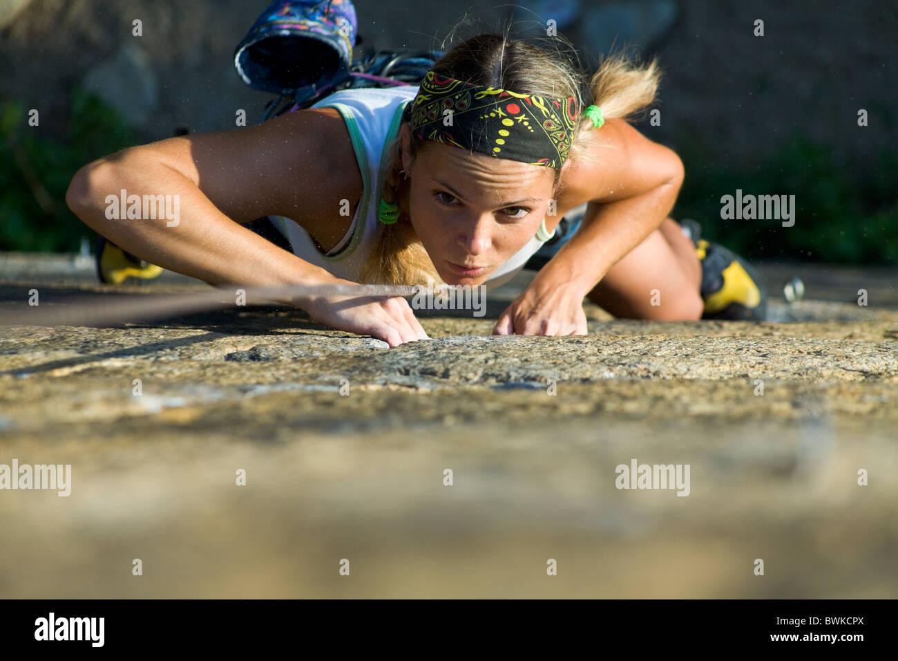 Jolie jeune fille monte une roche de granit Photo Stock