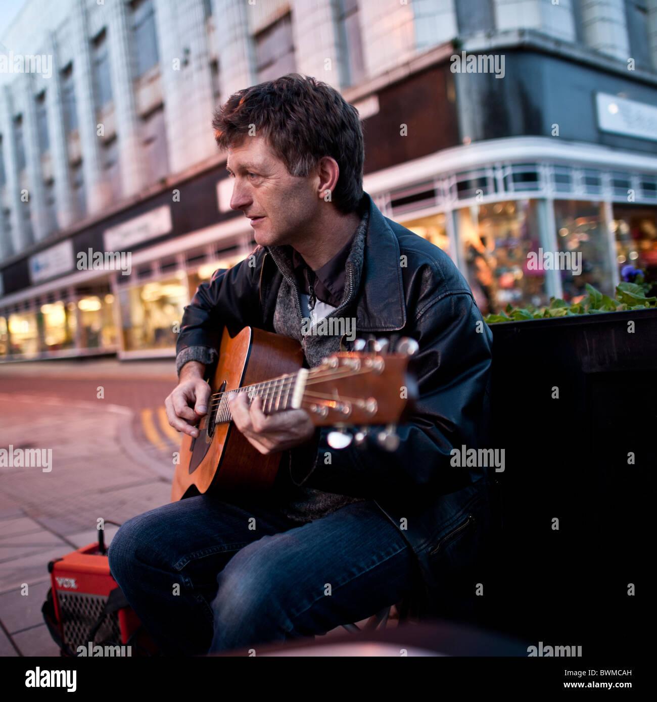 Un homme qui joue de la guitare de la rue dans les rues d'Aberystwyth, Pays de Galles UK Banque D'Images