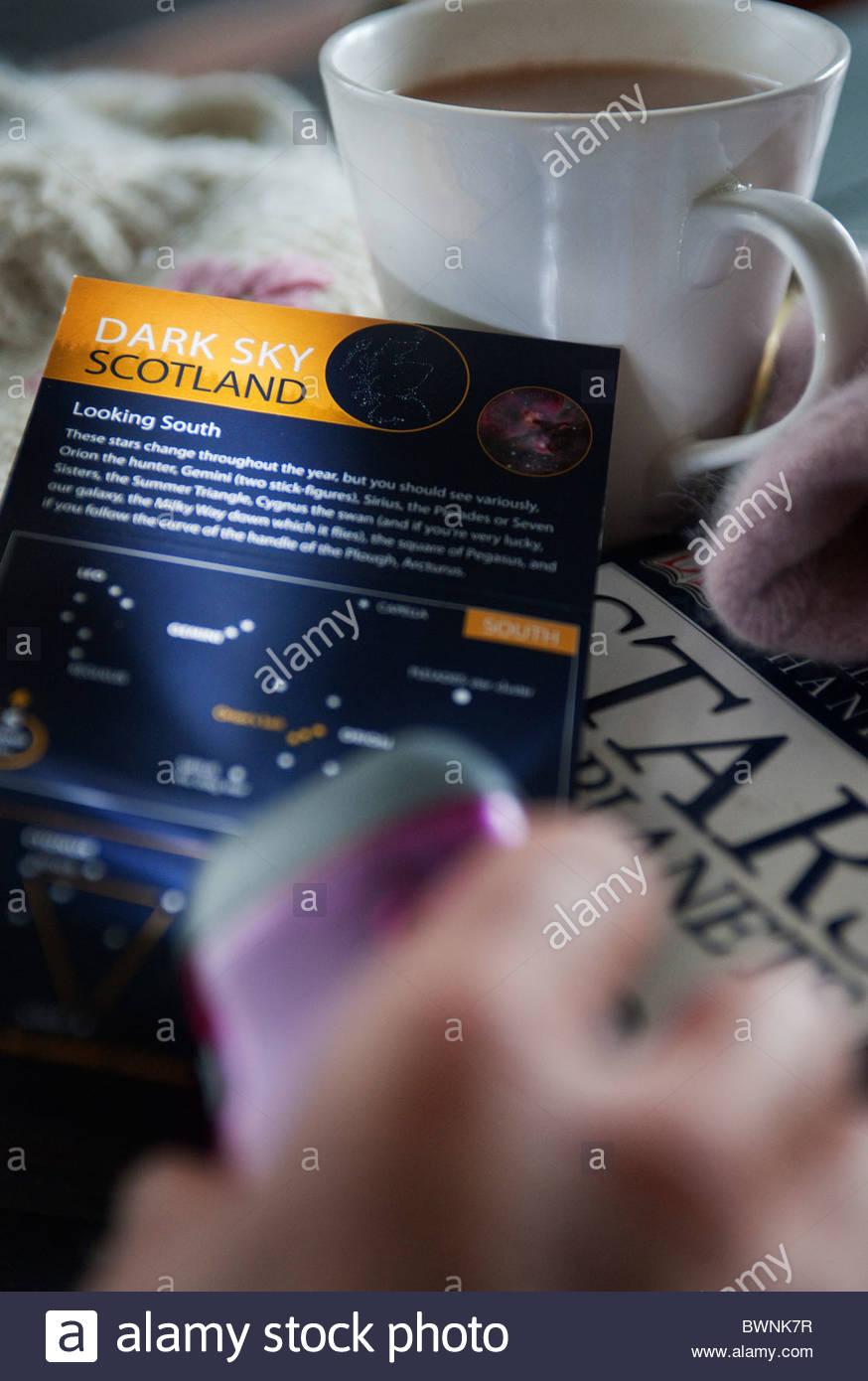 Main tenant flambeau, ciel sombre Écosse astrologie site, tasse de chocolat chaud et livre sur l'étoile. Photo Stock