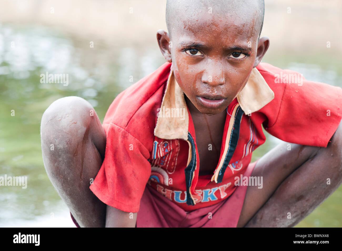 Indian street boy lave lui-même et de l'eau potable dans une rivière dans la campagne indienne. L'Andhra Photo Stock
