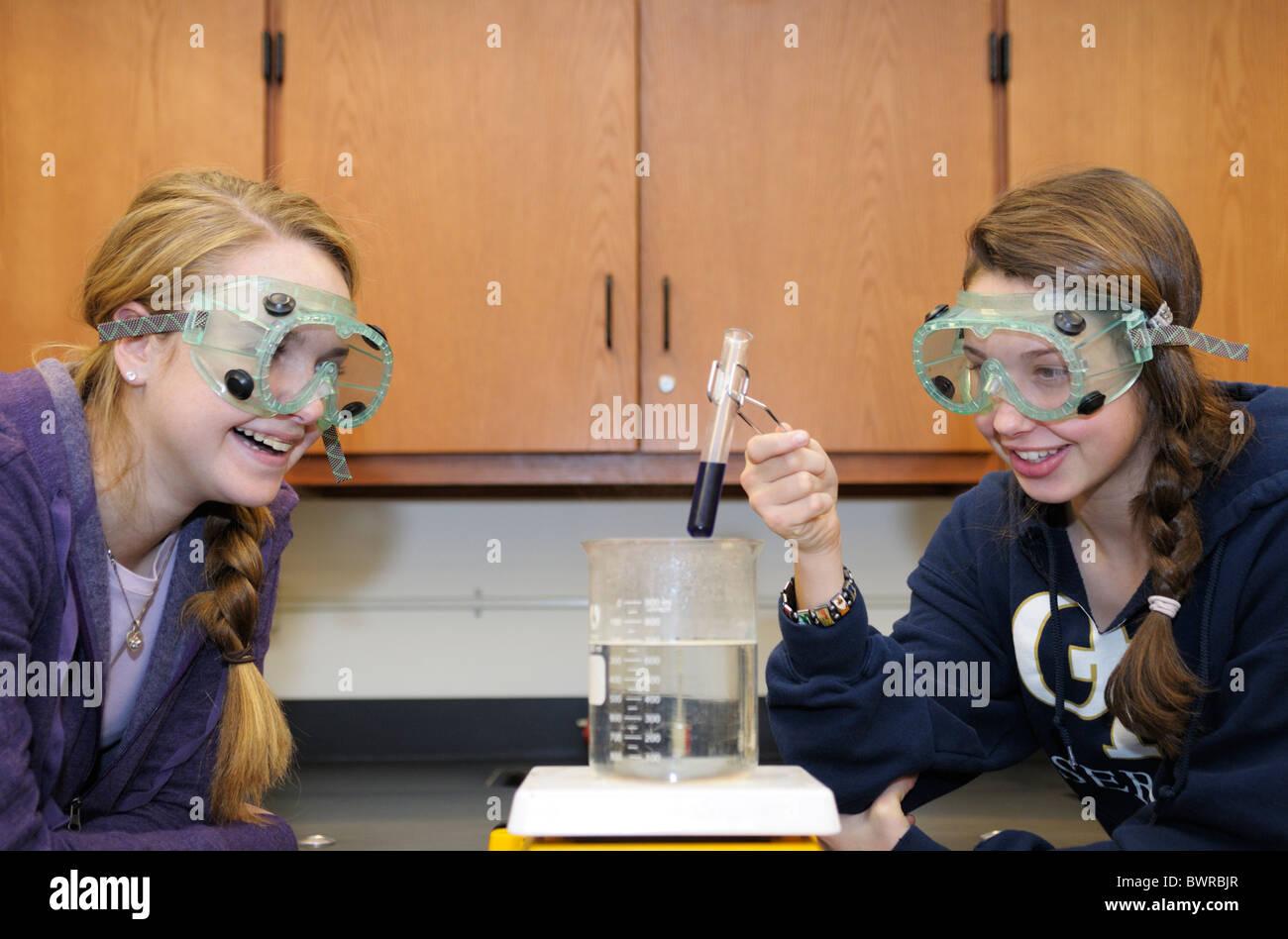 Les élèves portant des lunettes de sécurité tout en faisant une expérience scientifique Photo Stock