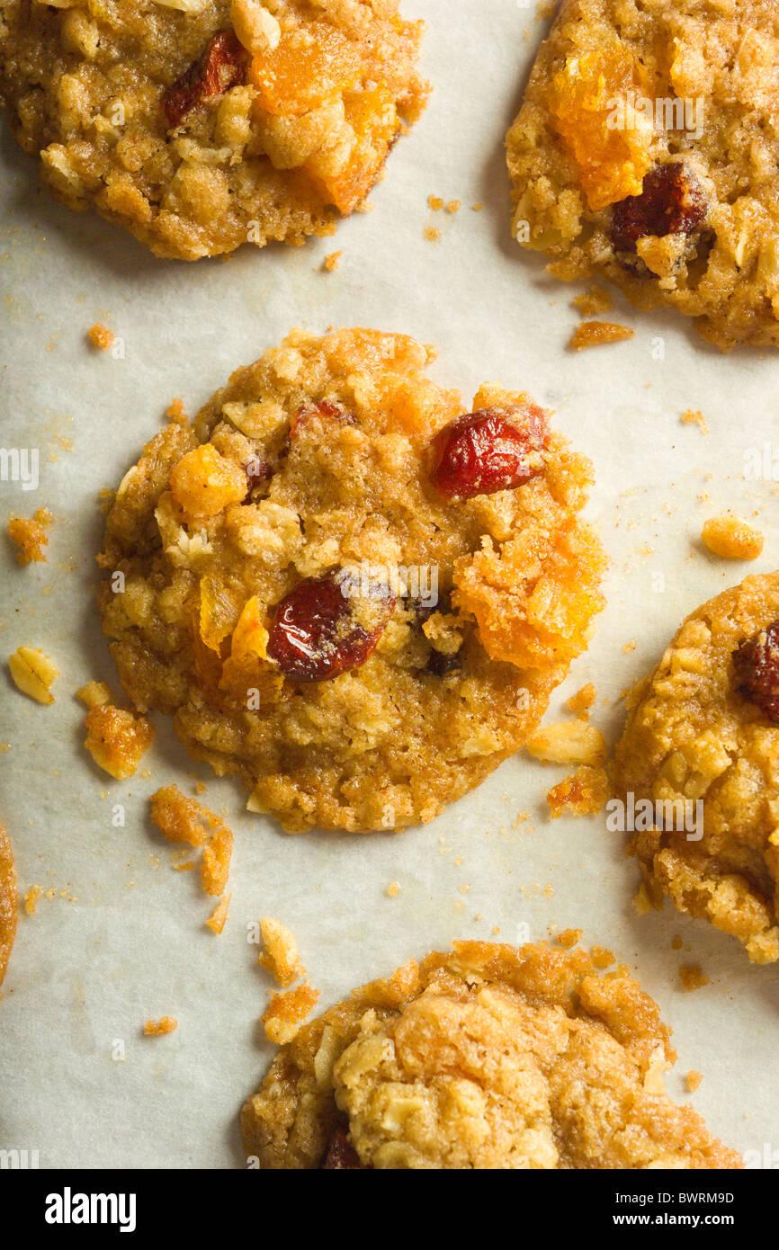 Abricots, canneberges, les biscuits. Juste cuits sur leurs feuilles et le papier parchemin. Photo Stock