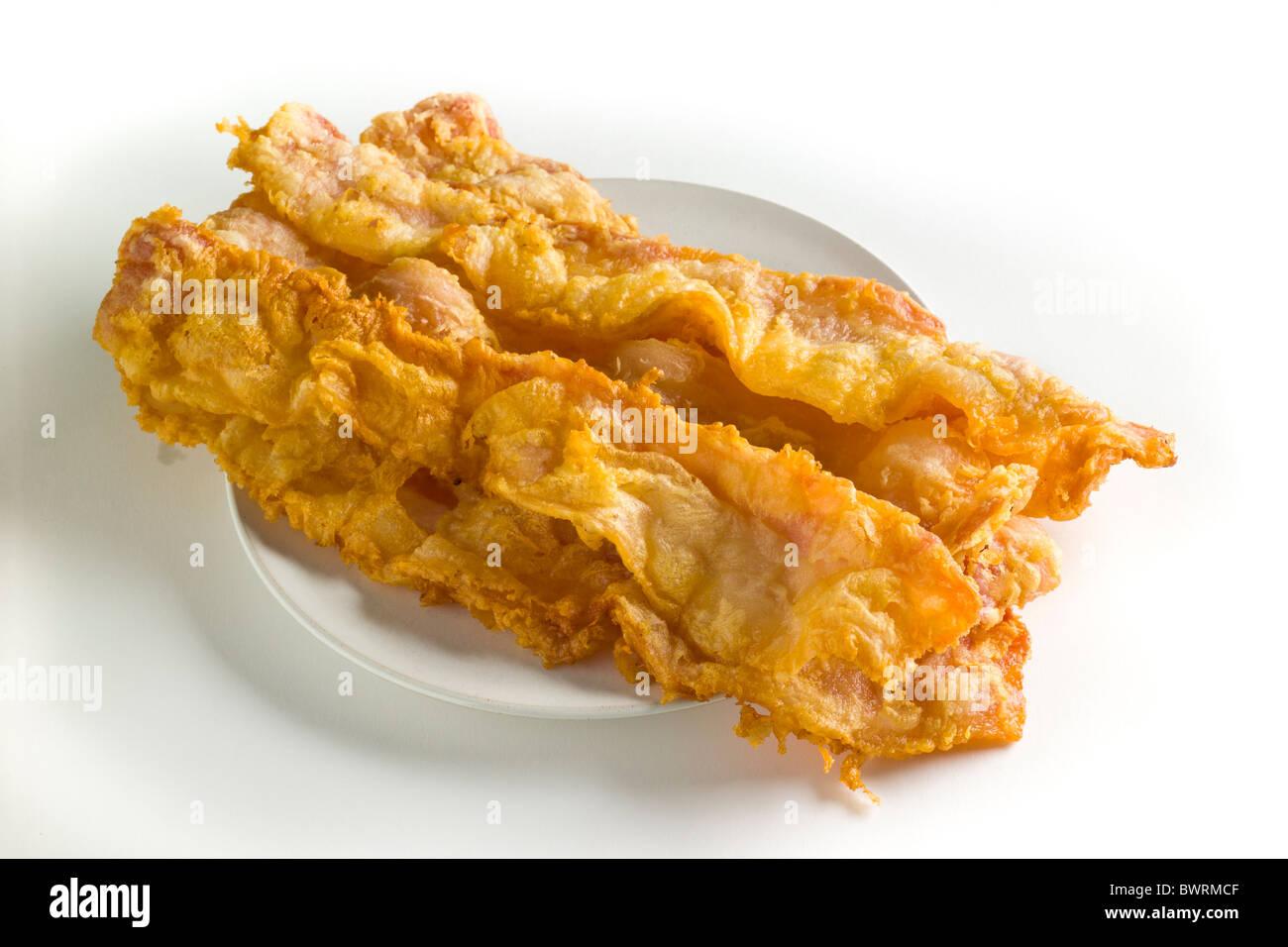 Chicken-Fried - tranches de bacon Bacon trempée dans un mélange de poudre de lait entier et de l'eau, Photo Stock