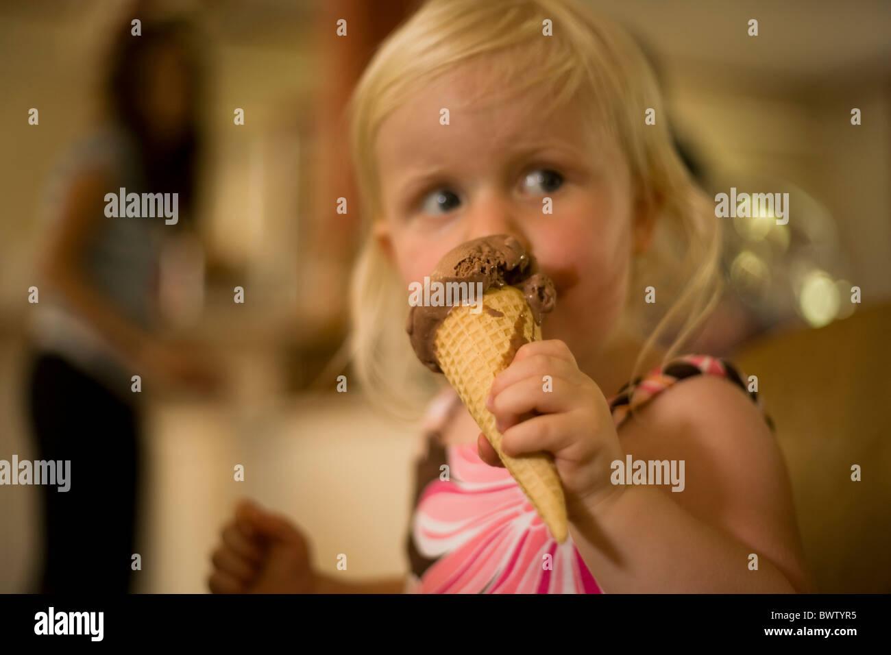 Petite fille blonde mange de la crème glacée au chocolat dans un cône Photo Stock