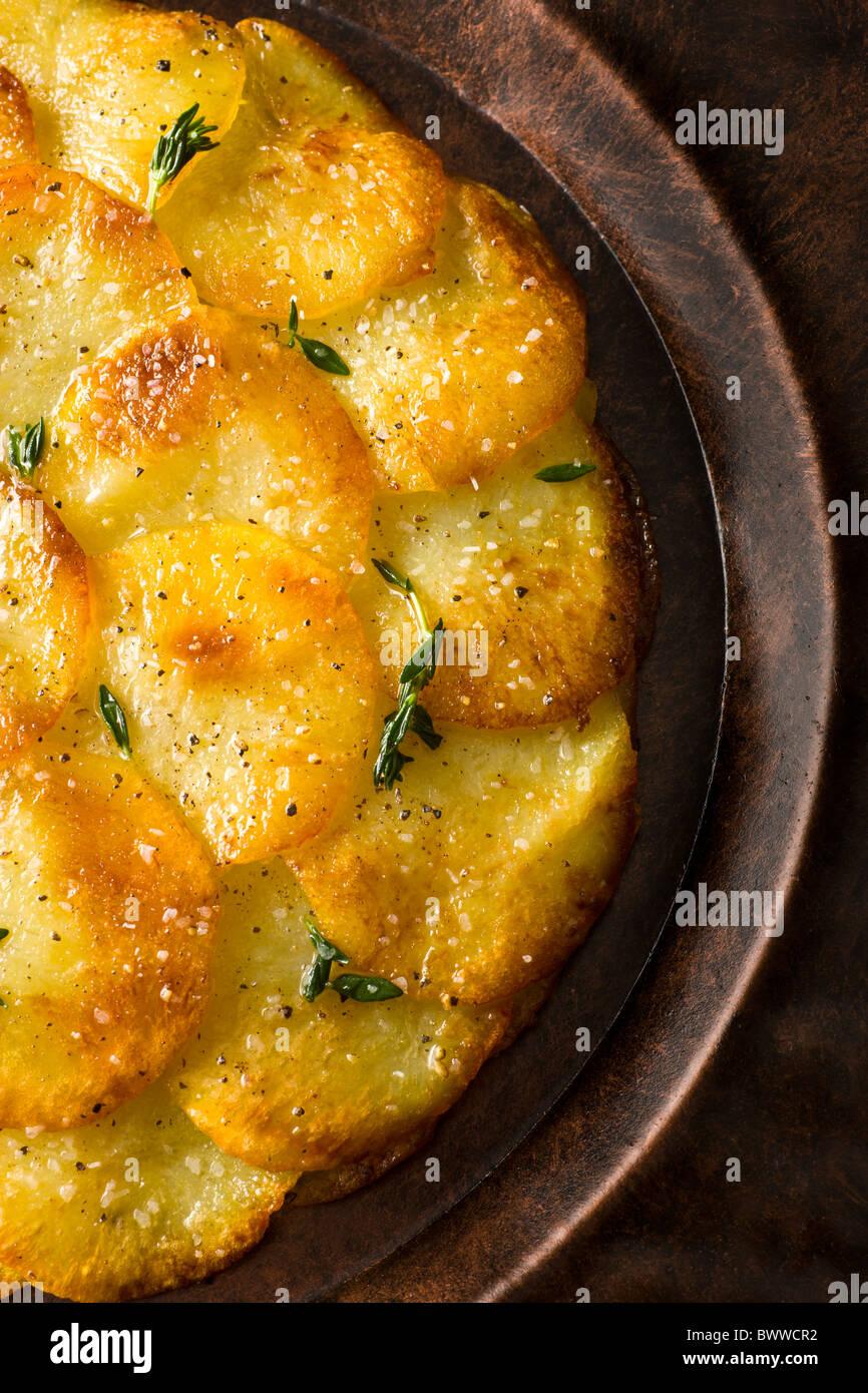 Galette de pomme de terre ou Anna garni de thym frais, sel et poivre et servi sur une plaque rustique. Banque D'Images