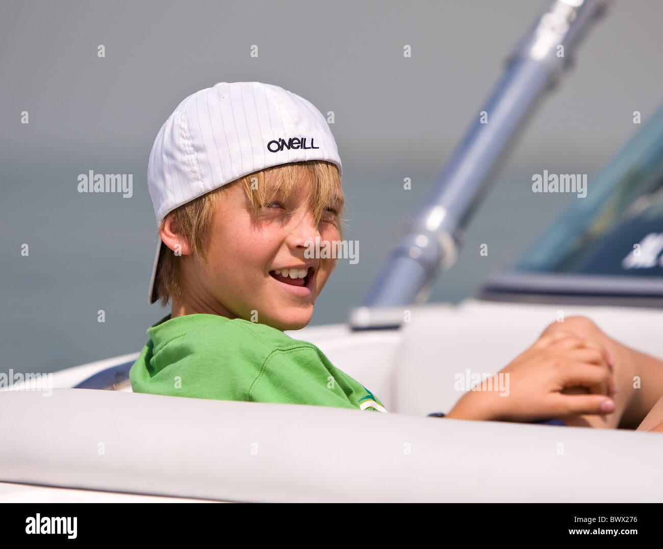 Effronté jeune garçon avec chapeau renversé assis dans un bateau de vitesse Photo Stock
