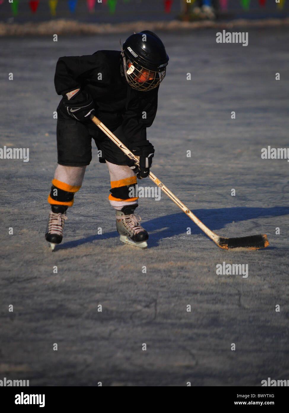 Enfant jouer au hockey sur glace sur la surface gelée du lac Houhai, Beijing, Chine Photo Stock