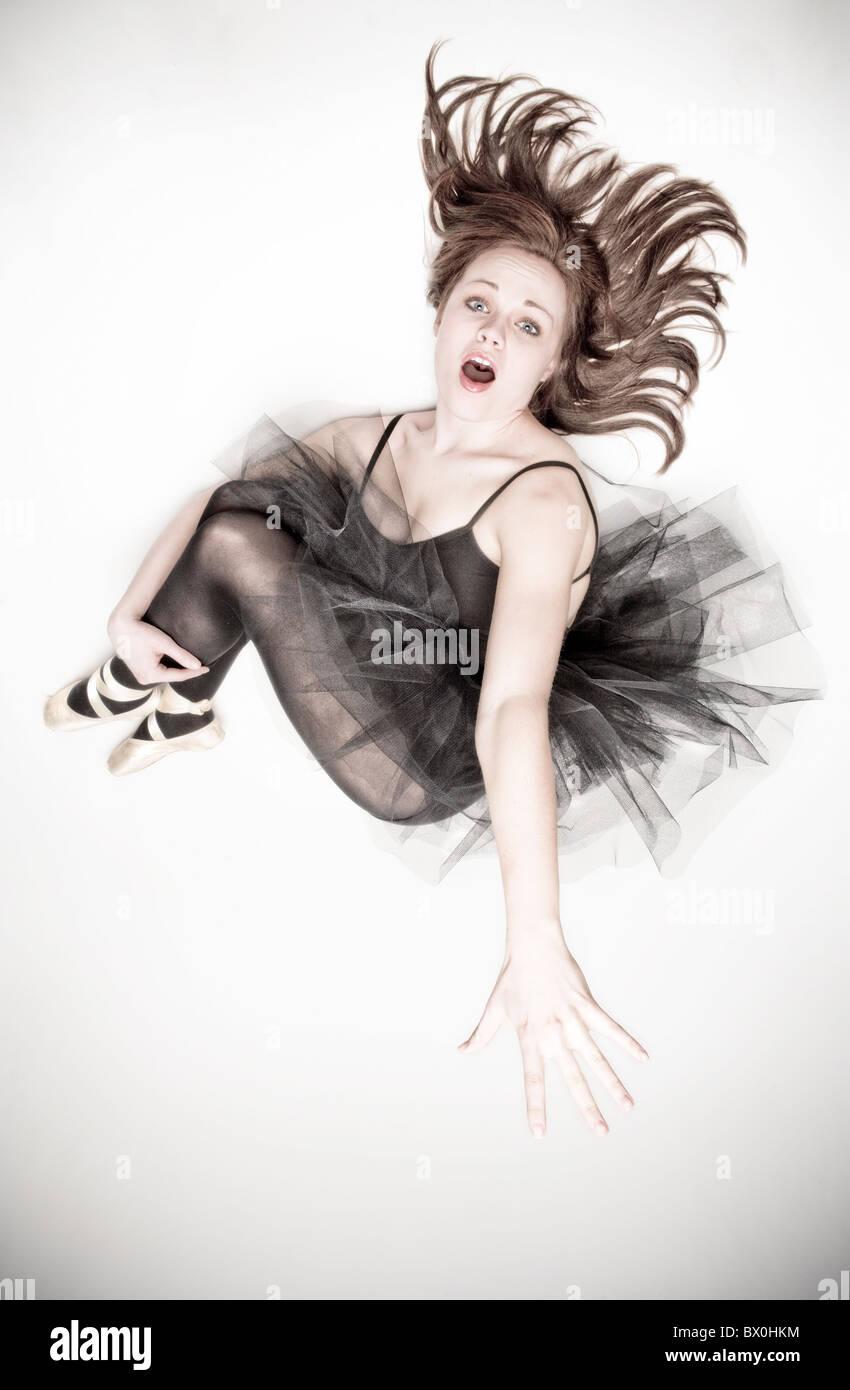 A young caucasian ballerina vêtu d'un tutu noir saute en l'air. Photo Stock