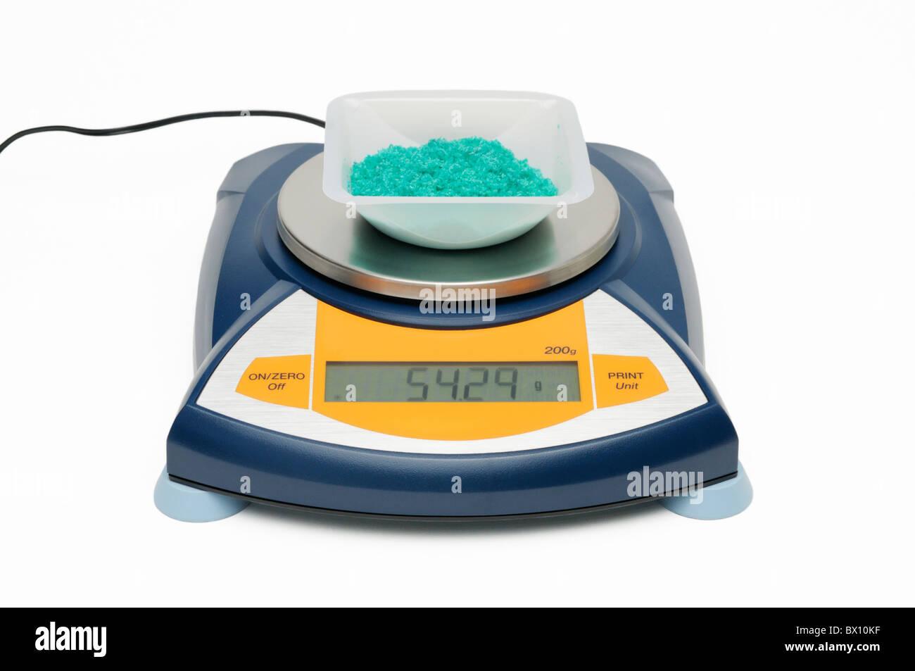 Mesure de la masse d'une substance chimique (chlorure cuivrique dihydraté cristaux) avec balance électronique Photo Stock