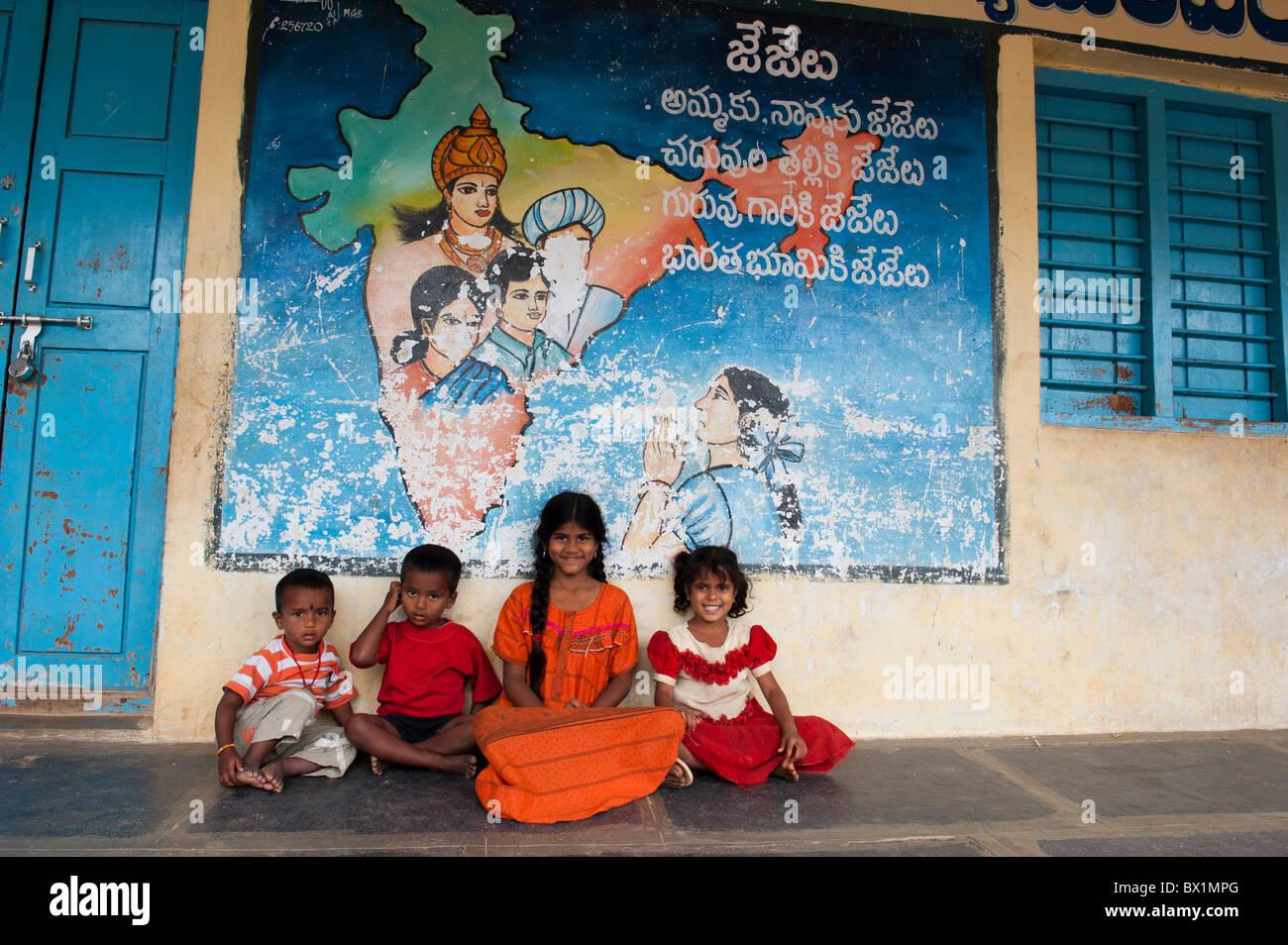 Les enfants indiens assis en face d'une carte colorée de l'inde la peinture sur un bâtiment indien, Photo Stock