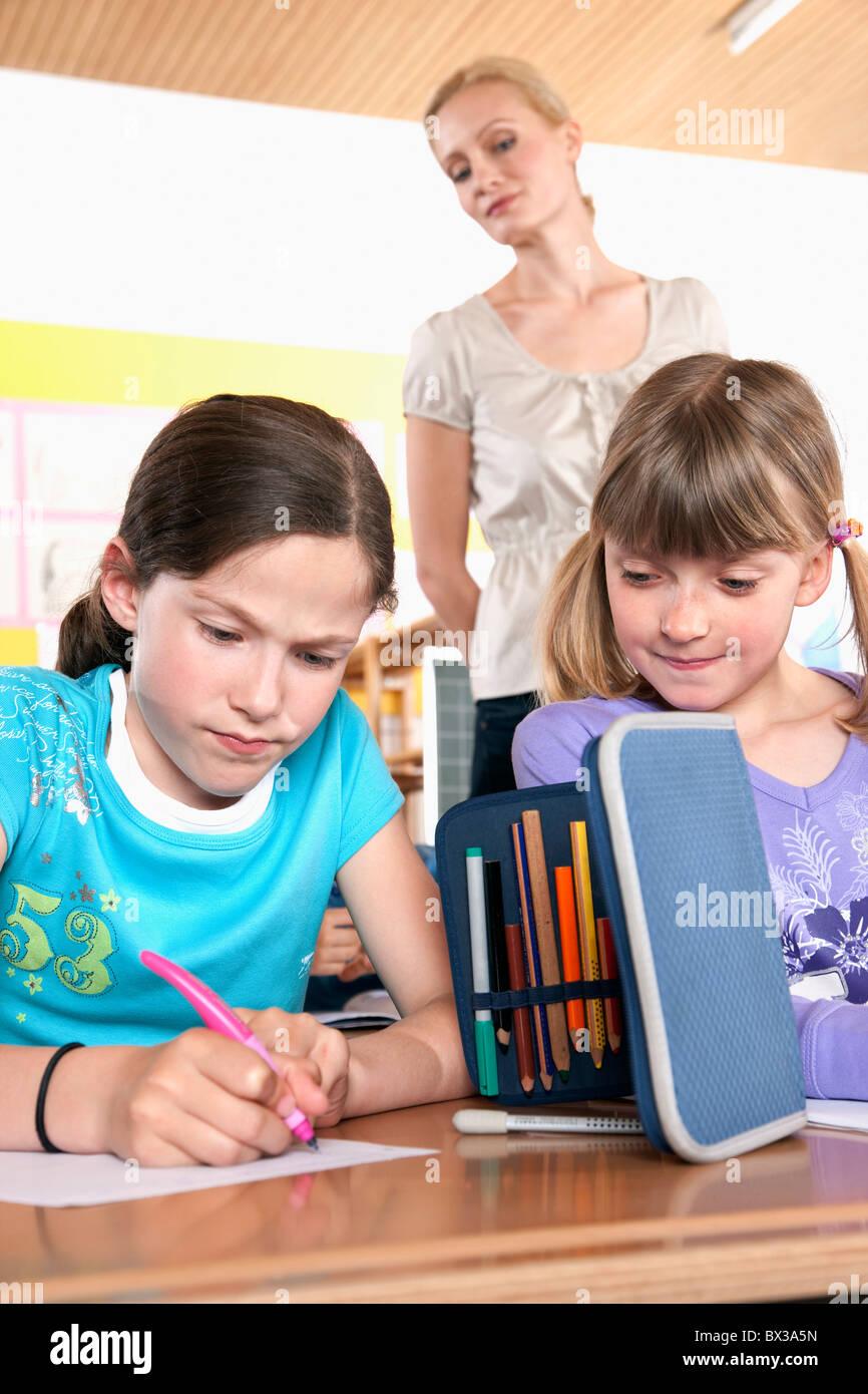 L'observation de l'enseignant deux jeunes filles test écrit Photo Stock