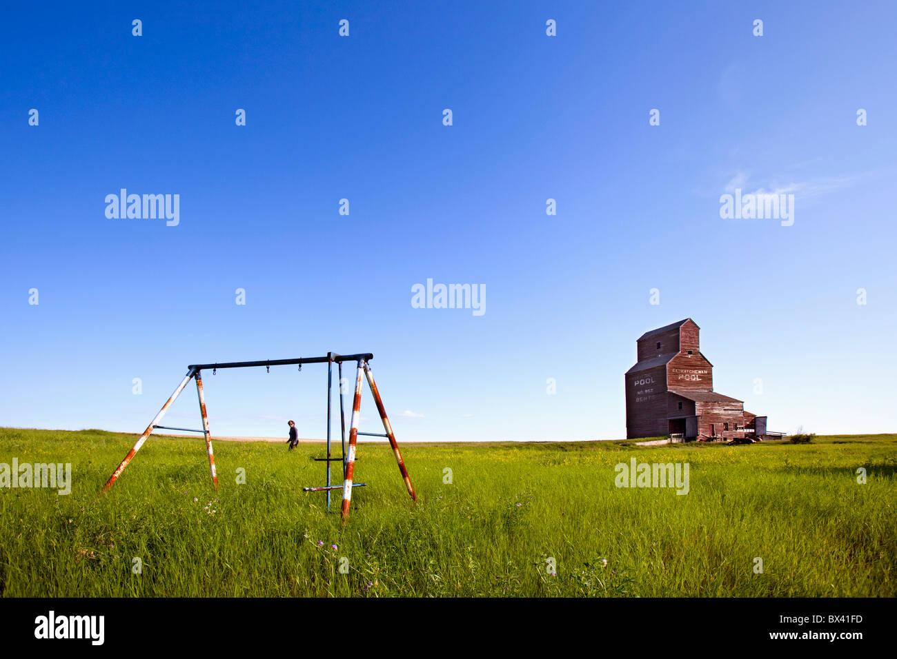 Un homme marche à travers un champ avec une vieille balançoire et un vieux grain elevator; virages, Photo Stock