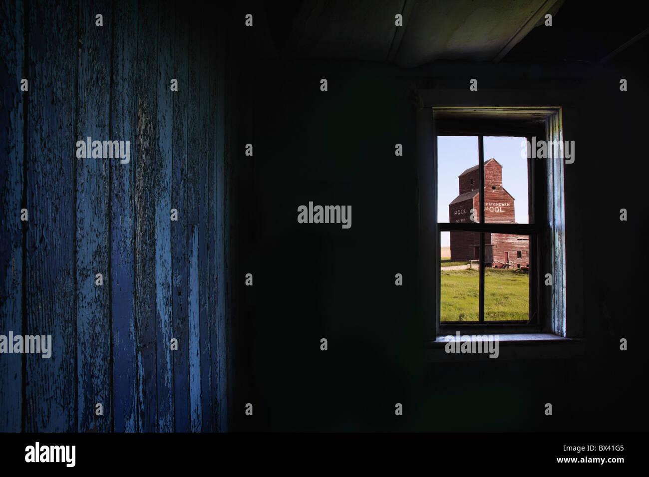 Un élévateur à grains vus à travers la fenêtre d'une vieille ville fantôme abandonnée; Photo Stock