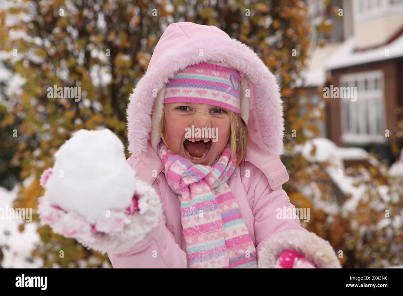 Une jeune fille espiègle prêt à jeter une boule de neige Photo Stock
