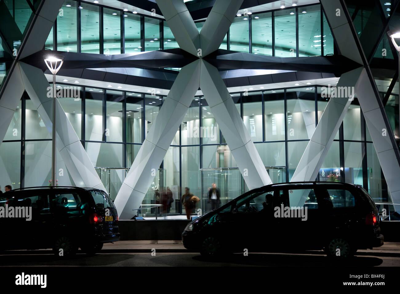 Voitures garées devant un bureau futuriste building at night, St Mary Axe, le cornichon, le Swiss Re building Banque D'Images