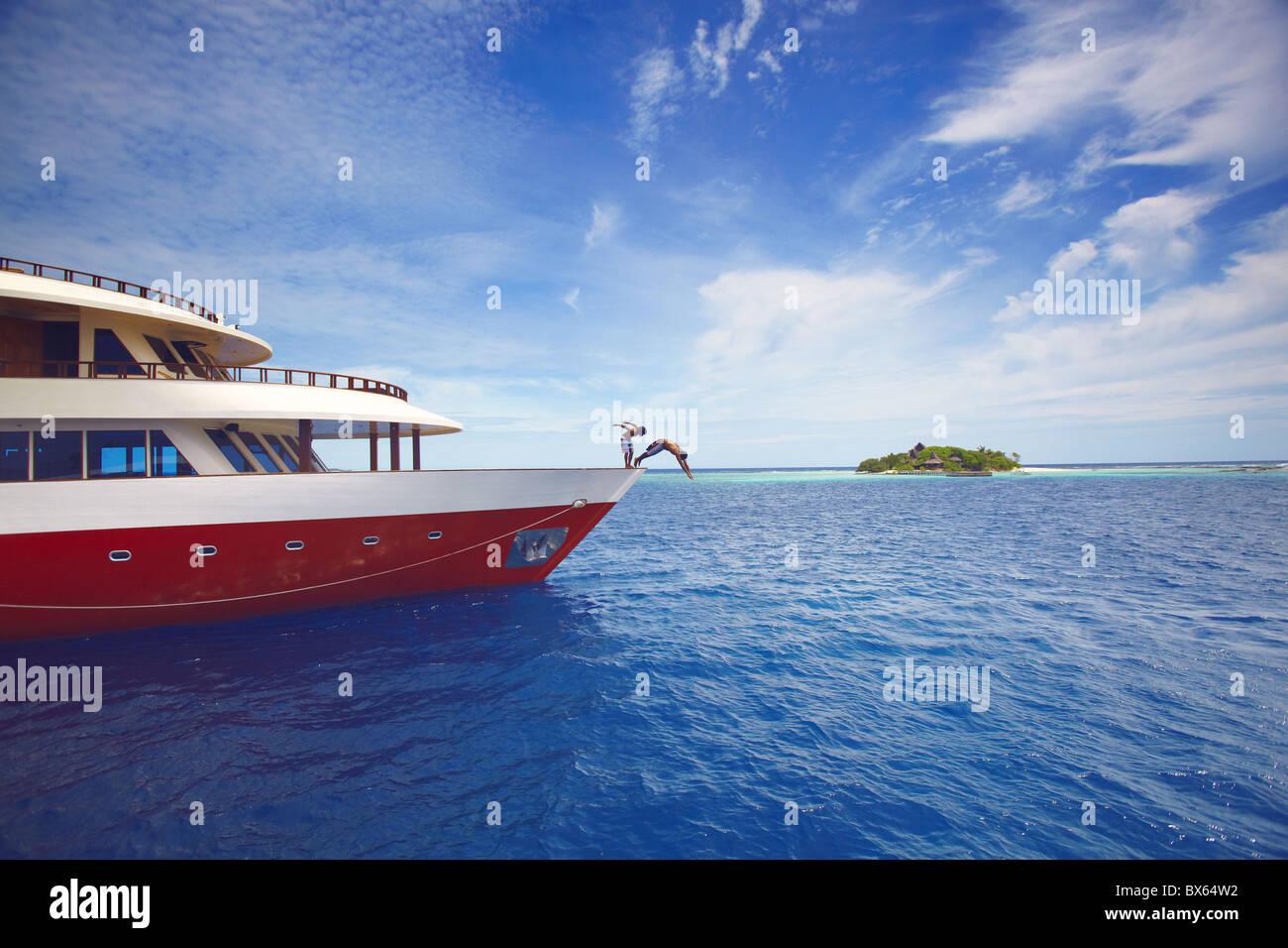 Les jeunes sauter de bateau en mer, Maldives, océan Indien, Asie Photo Stock