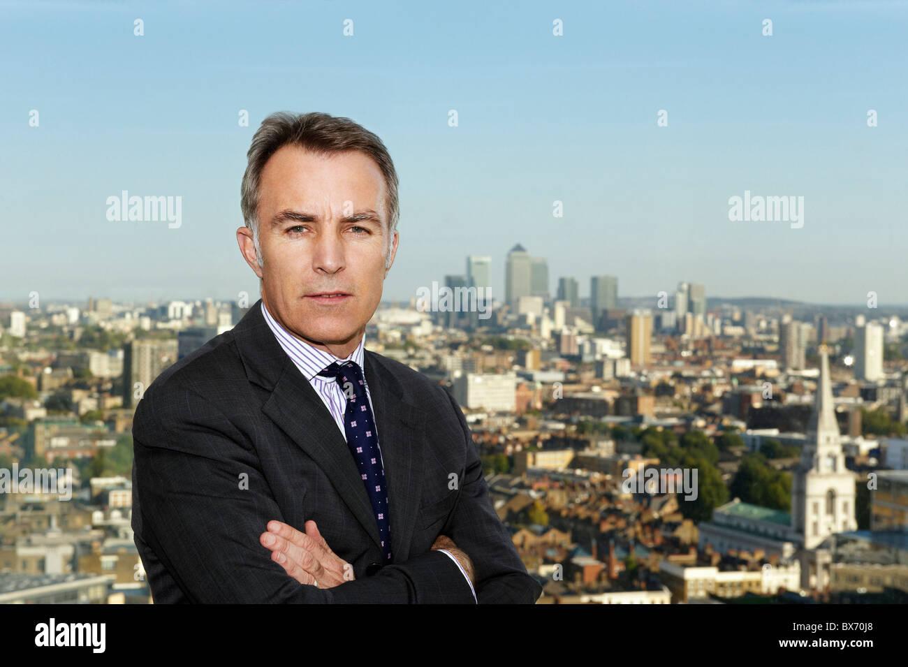 Portrait de l'exécutif avec vue de paysage de ville derrière lui Photo Stock