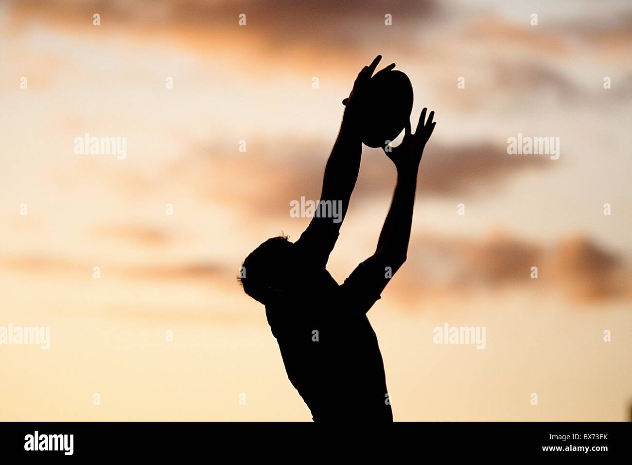 Silhouette Rugby player with ball avec coucher de soleil Photo Stock