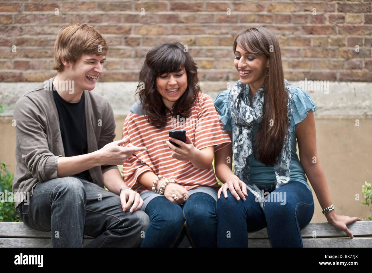 Le partage d'amis blague sur mobiles à l'extérieur Photo Stock