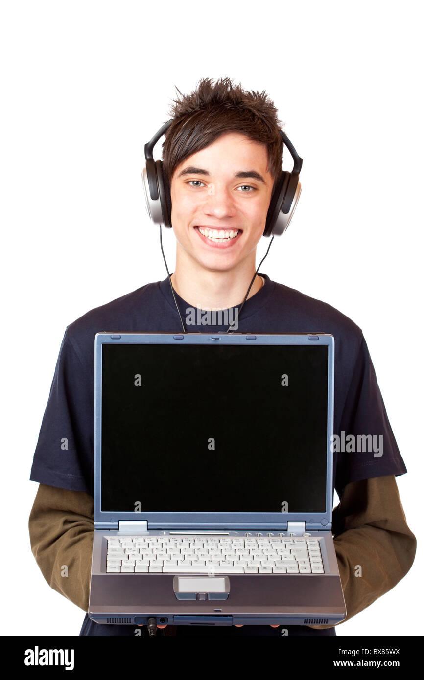 Adolescent mâle avec Internet fait écouteurs mp3 musique à télécharger sur ordinateur. Photo Stock