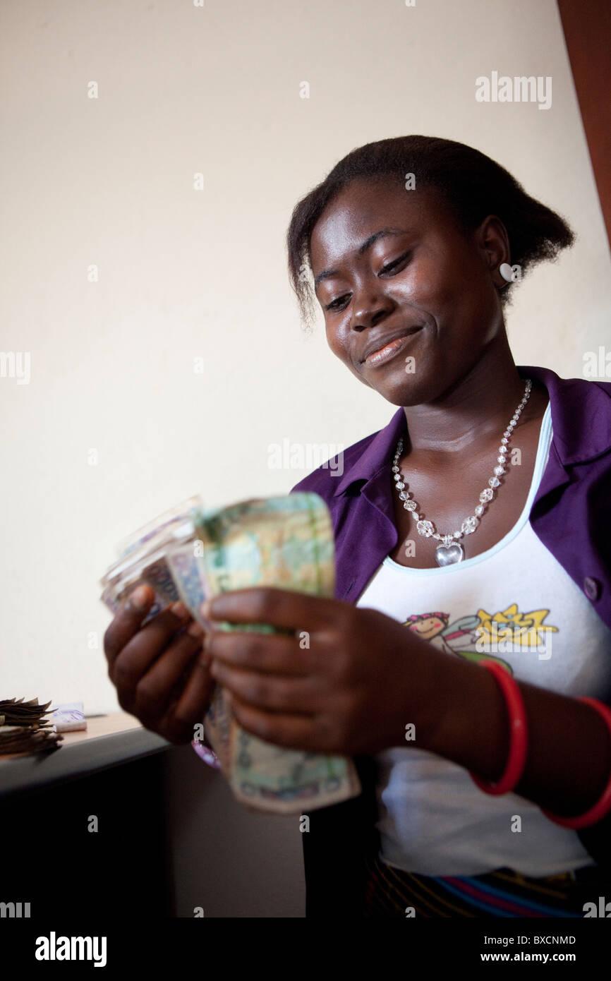Une femme compte paiement après avoir reçu un prêt de microfinance à Freetown, Sierra Leone, Afrique de l'Ouest. Banque D'Images