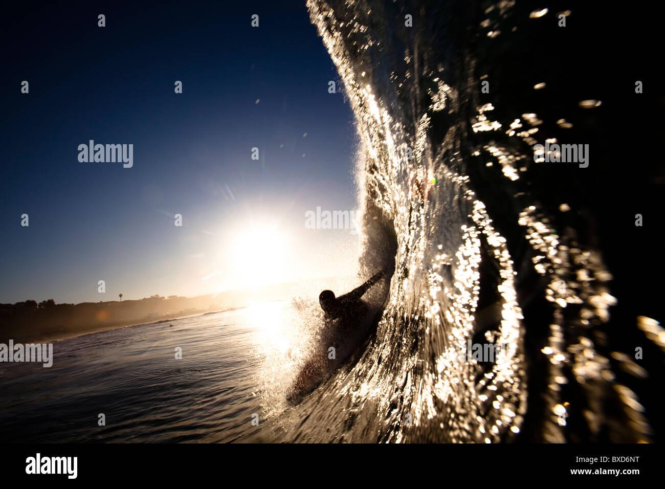 Un surfeur mâle tire dans un tonneau à Zuma beach à Malibu, en Californie. Photo Stock