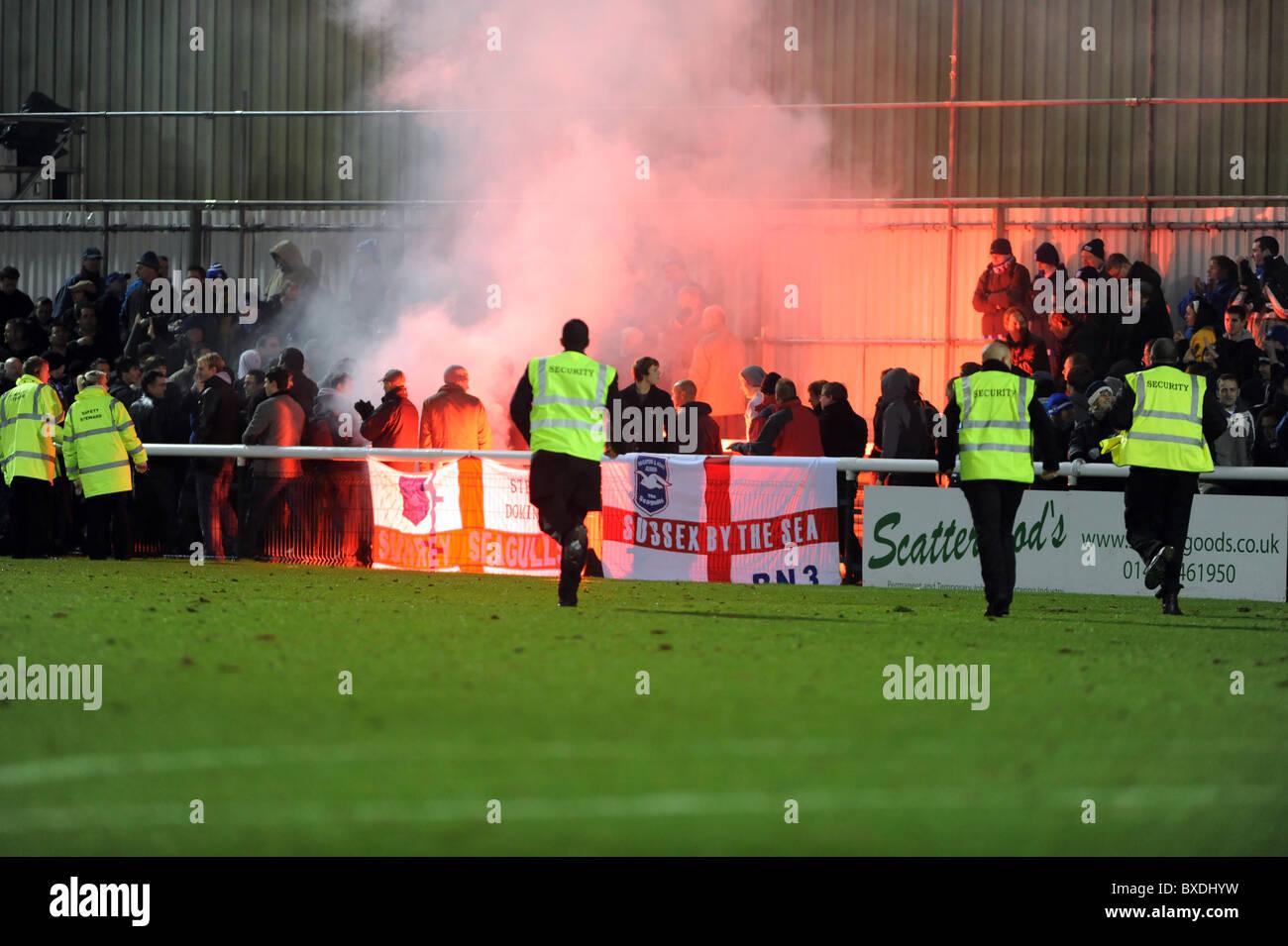 Le club de football de Woking, stewards se précipiter au loin fans après que l'un d'eux vous permet de désactiver une poussée après le match terminé Banque D'Images